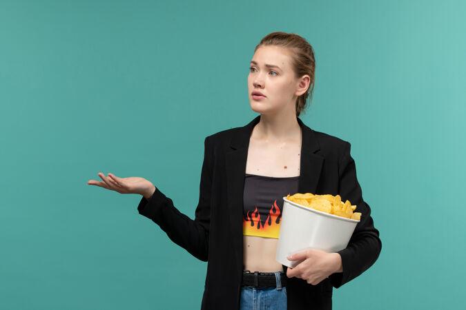 正面图年轻女性在蓝色的水面上吃薯片看电影