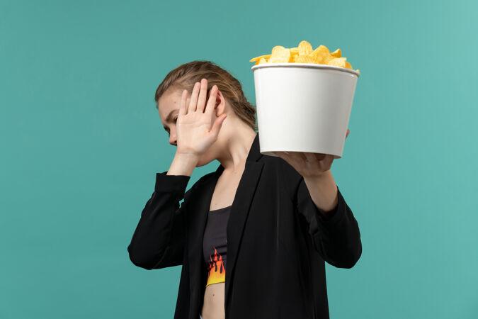 正面图:年轻女性在蓝色桌子上吃薯片看电影