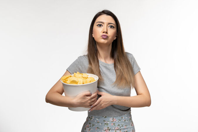 正面图年轻的女性正在吃薯片 在浅白色的表面上看电影