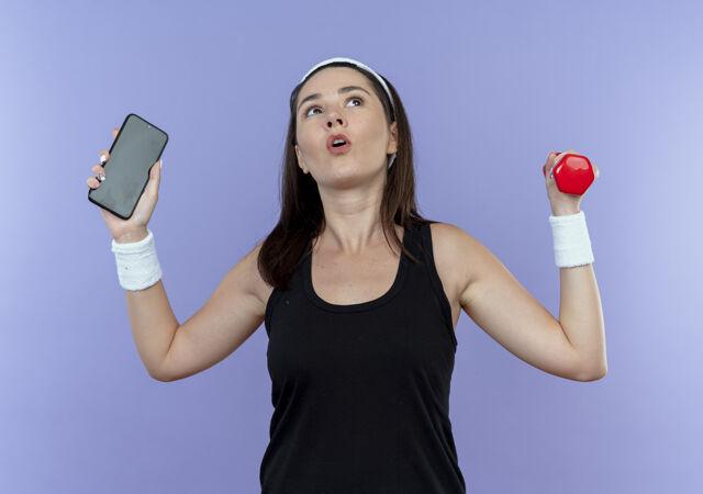 戴着头巾 手持智能手机和哑铃的年轻健身女士站在蓝色的墙上 看起来很困惑