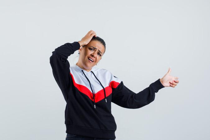 年轻的女性手放在头上 一边指着旁边 穿着五颜六色的运动衫 神情迷茫 前视图
