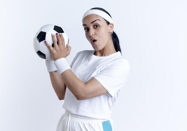 年轻惊讶的白人运动女性戴着头带和腕带拿着球在白色空间与复制空间隔离