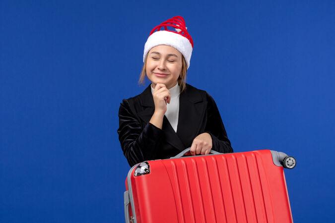 正面图年轻女子背着红包在蓝色墙上度假旅游的女人