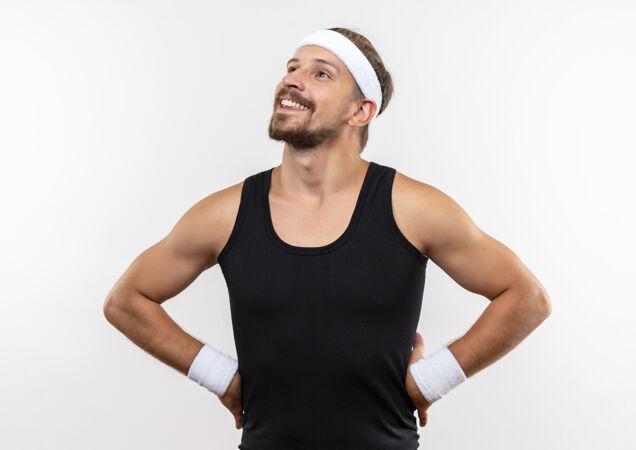 面带微笑的年轻帅气的运动型男人戴着头带和腕带 双手放在腰上仰望 隔离在白色的空间里