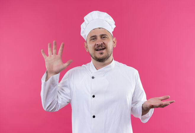微笑着的年轻帅哥厨师身着厨师制服 在粉红色的空间里展示着空空的双手