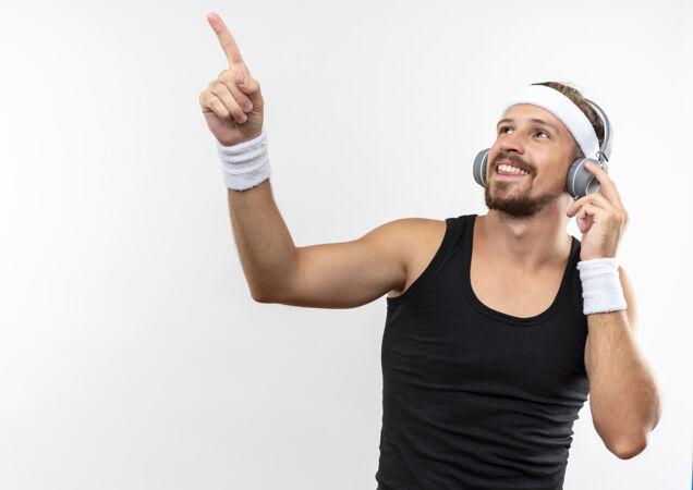 面带微笑的年轻帅气的运动型男人戴着头带和腕带 戴着耳机看着 指着头 一只手放在耳机上隔离在空白处