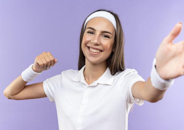 面带微笑的漂亮运动女孩戴着头带和腕带伸出手握紧拳头孤立在紫色的空间