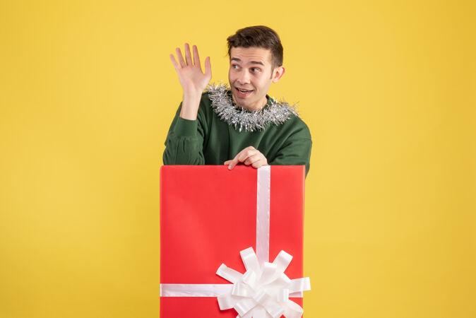 正面图年轻人招呼某人站在黄色的大礼品盒后面
