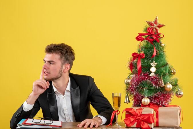 正面图:坐在黄色工作台后面的男工人