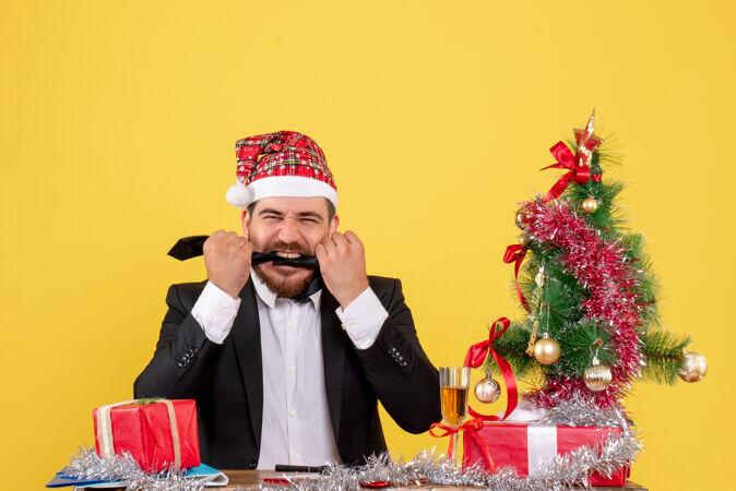 正面图男性工人坐在桌子后面 黄色的桌子上放着礼物