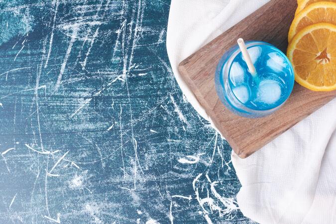 橘子片和一杯饮料放在蓝色的上面