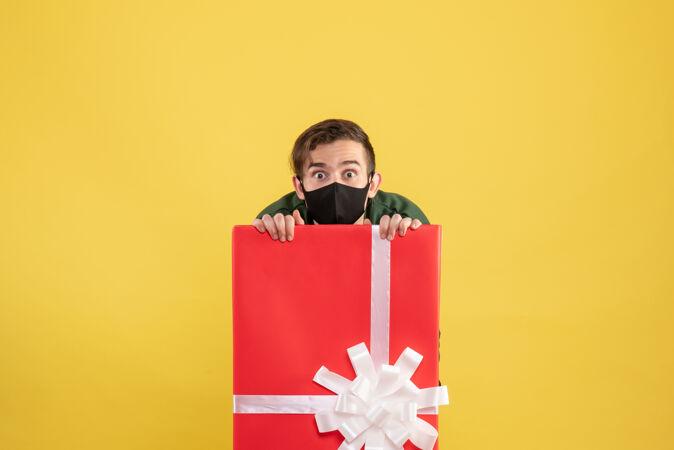 正面图戴着面具的大眼睛男人藏在黄色的大礼品盒后面